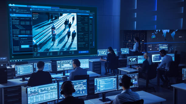 Team of Professional Cyber Security Data Science Engineers Work on Surveillance Tracking Shot of People Walking on City Streets. Big Dark Control and Monitoring Room with Computer Displays. stock photo