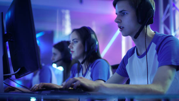 team of professional esport gamers playing in competitive video games on a cyber games tournament. they talk to each other into microphones. - esports stock photos and pictures