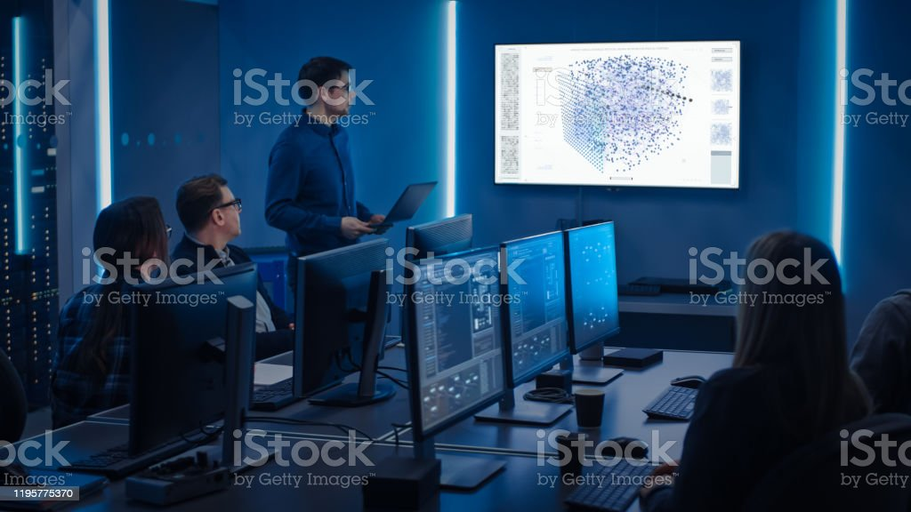 Team of Professional IT Developers Have a Meeting, Speaker Talks about New Blockchain Based Software Development Shown on TV. Concept: Software Development, Deep Learning, Artificial Intelligence, Data Mining Team of Professional IT Developers Have a Meeting, Speaker Talks about New Blockchain Based Software Development Shown on TV. Concept: Software Development, Deep Learning, Artificial Intelligence, Data Mining Adult Stock Photo