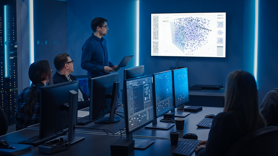Team Of Professional It Developers Have A Meeting Speaker Talks About New Blockchain Based Software Development Shown On Tv Concept Software Development Deep Learning Artificial Intelligence Data Mining Stock Photo - Download Image Now