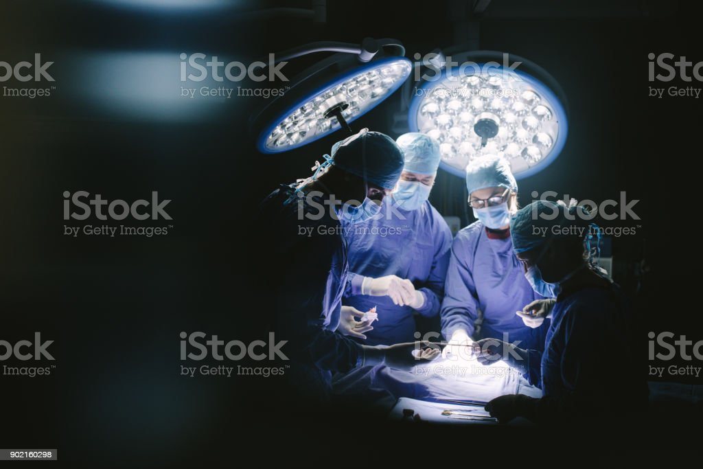 Team of professional surgeons performing surgery stock photo