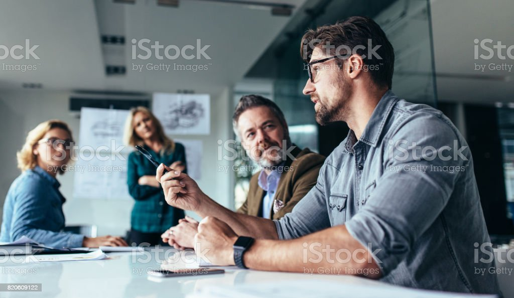 Team of professionals discussing over new business project stock photo
