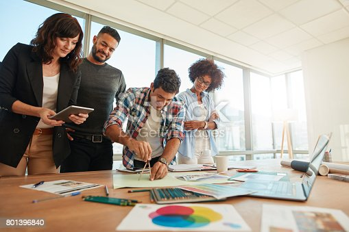 848290020istockphoto Team of professionals working together in creative office 801396840