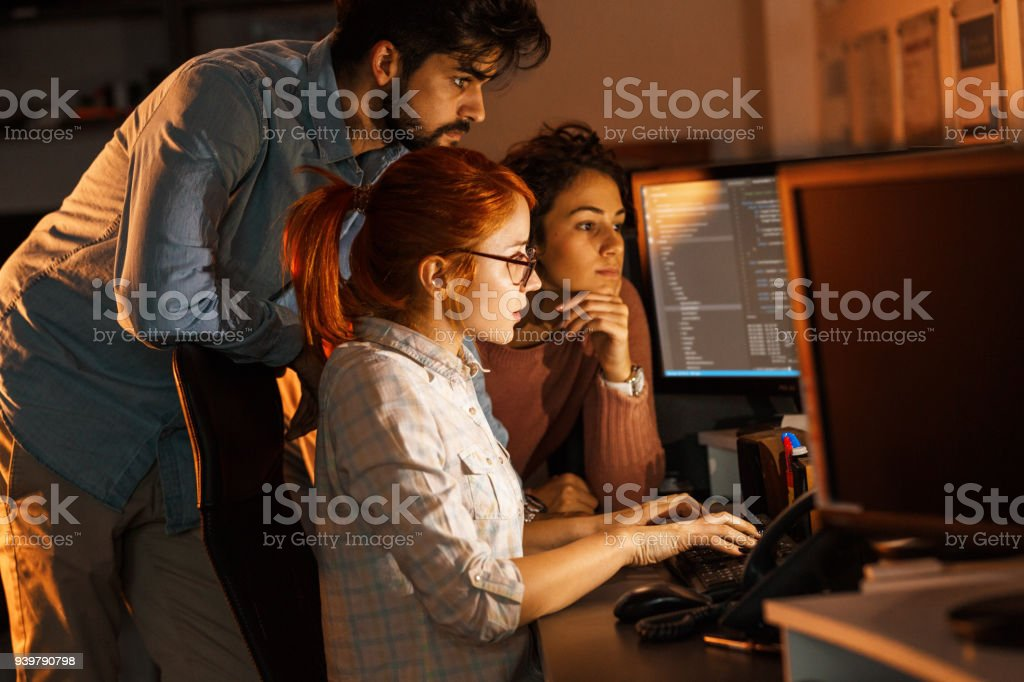 Team of programmers working on new project.They working late at night at the office. stock photo