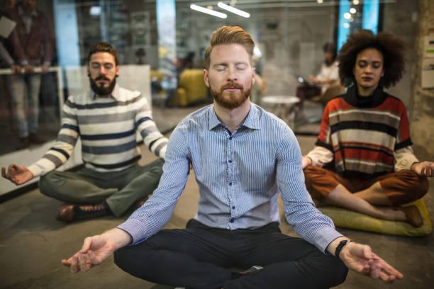 team von entspannten business-leute, die ausübung von yoga im casual büro. - yoga fürs büro stock-fotos und bilder