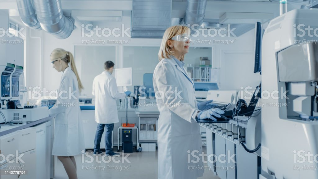 Team of Research Scientists Working On Computer, with Medical Equipment, Analyzing Blood and Genetic Material Samples with Special Machines in the Modern Laboratory. - Стоковые фото Анализировать роялти-фри