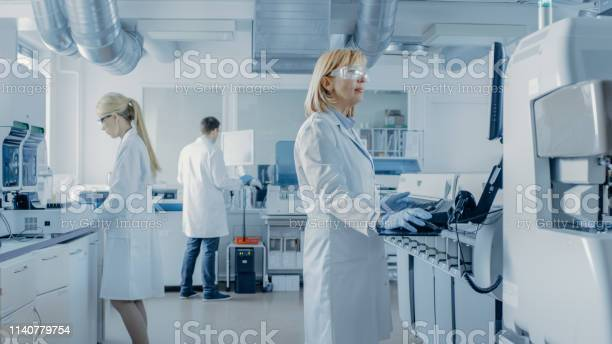 Team Of Research Scientists Working On Computer With Medical Equipment Analyzing Blood And Genetic Material Samples With Special Machines In The Modern Laboratory — стоковые фотографии и другие картинки Анализировать
