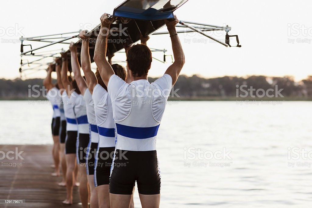Team of rowers carrying a crew canoe over heads royalty-free stock photo