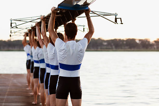 Team of rowers carrying a crew canoe over heads stock photo