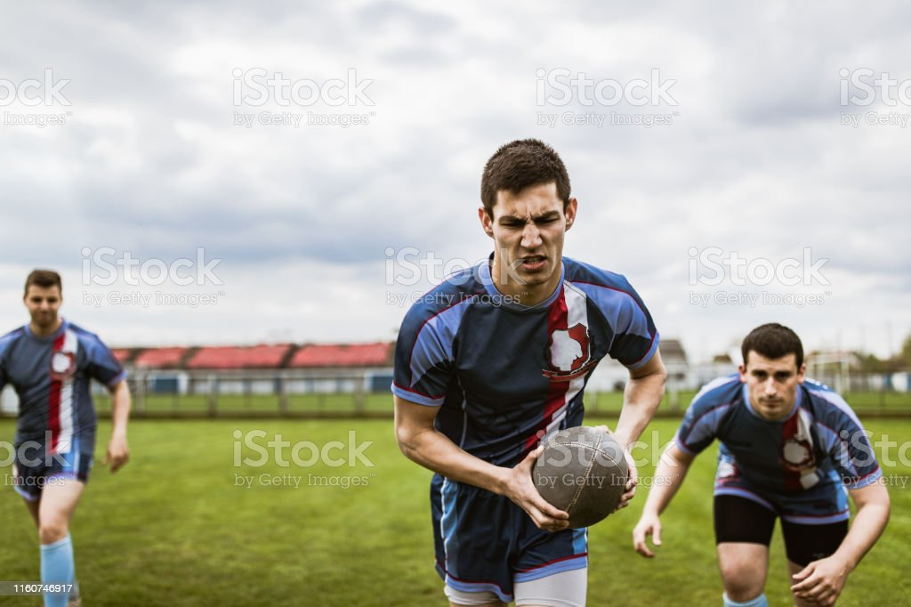 Determined rugby players running with ball on a playing field. Copy...
