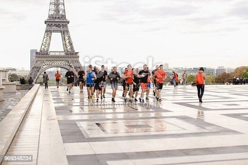 Team of runners running in Eiffel Tower background on Trocadero square, Paris. Concept of sport competition in Europe and France.