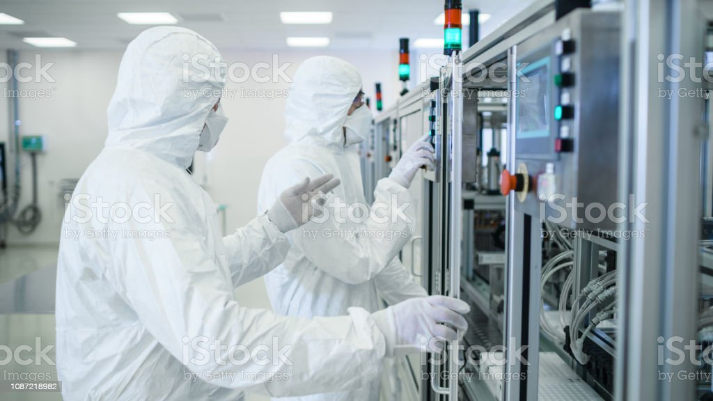 Team of Scientists in Sterile Protective Clothing Work on a Modern Industrial 3D Printing Machinery. Pharmaceutical, Biotechnological and Semiconductor Creating / Manufacturing Process. stock photo