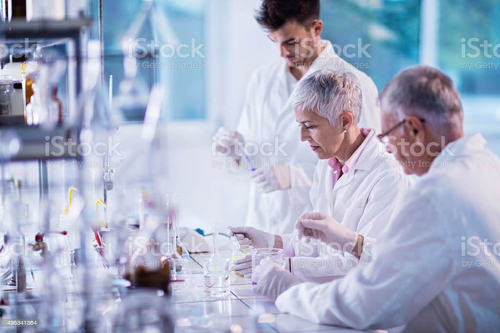 Team of scientists working on new scientific research in laboratory. stock photo
