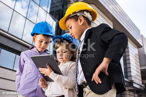 643843490istockphoto Team of small architects working on digital tablet outdoors. 613336584