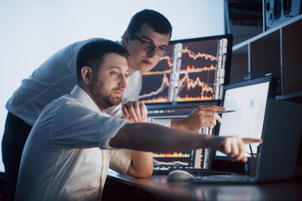Team der Börsenmakler hat in einem dunklen Büro mit Bildschirmen ein Gespräch geführt. Analyse von Daten, Grafiken und Berichten für Investitionszwecke. Kreative Teamwork-Händler – Foto