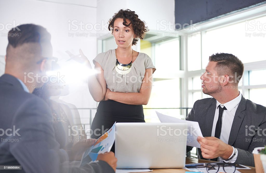 team of successful business people having a meeting in executive Candid photo of a corporate businesspeople group discussing strategies in professionnal indoors setting. Adult Stock Photo