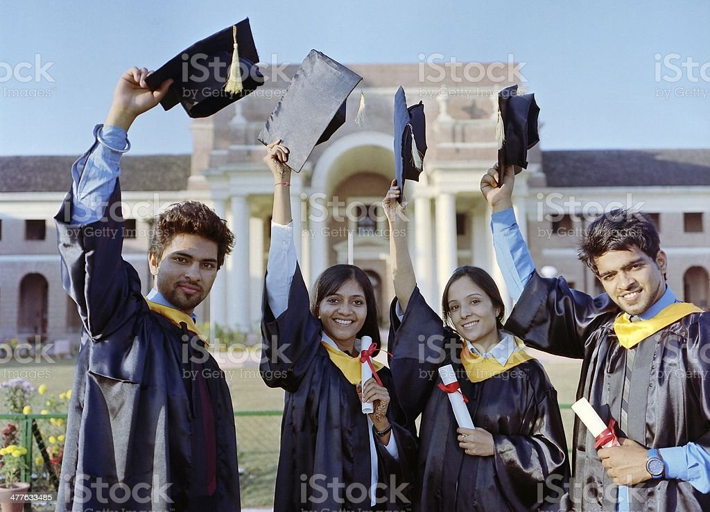 Team of successful university graduates raising their convocation caps. stock photo