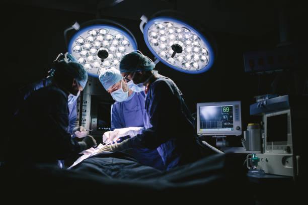 Team of surgeons doing surgery stock photo