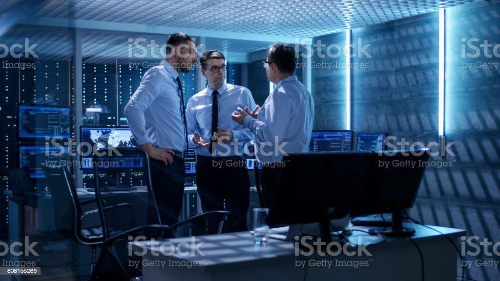 Team von technischen Moderatoren haben aktive Diskussion im Überwachungsraum. System Control Room ist voller arbeiten zeigt zeigt verschiedene Daten und Server-Racks hat. - Lizenzfrei Abenddämmerung Stock-Foto