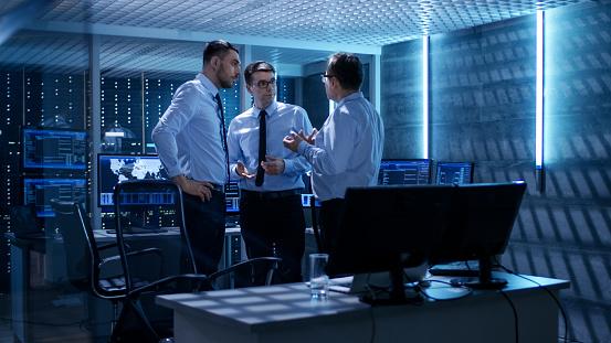 Team Von Technischen Moderatoren Haben Aktive Diskussion Im Überwachungsraum System Control Room Ist Voller Arbeiten Zeigt Zeigt Verschiedene Daten Und Serverracks Hat Stockfoto und mehr Bilder von Abenddämmerung