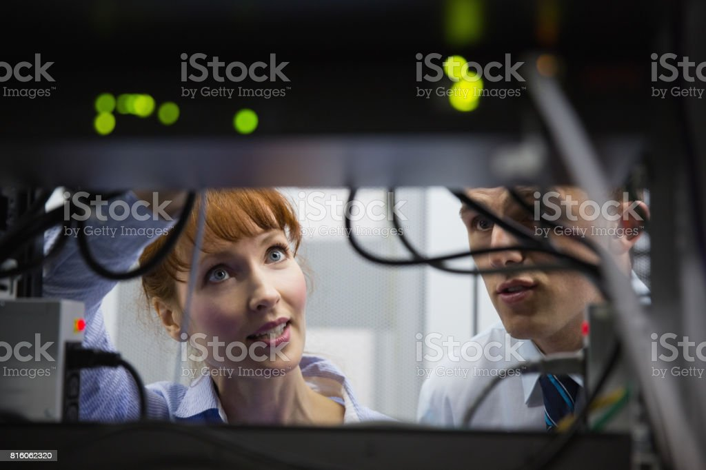 Team of technicians talking and looking at server stock photo
