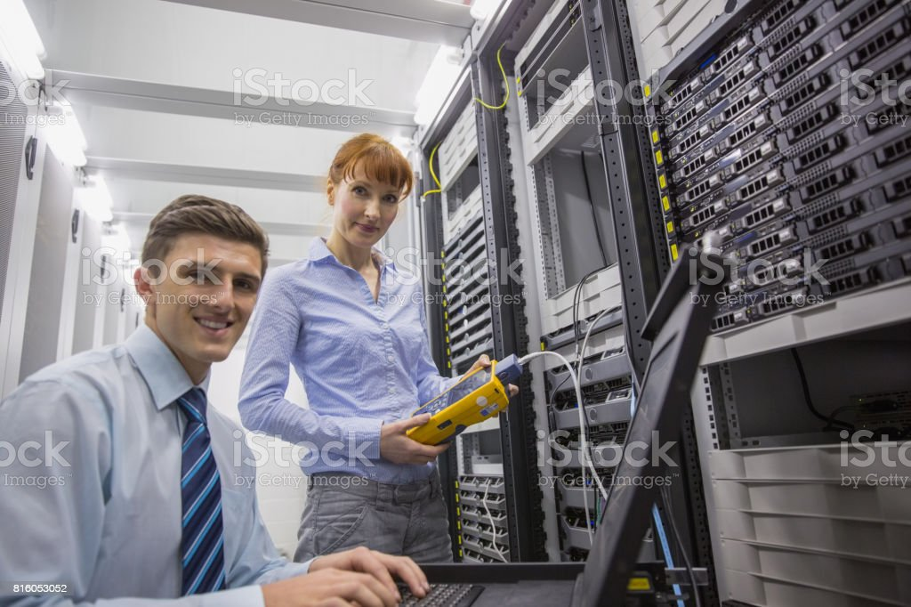 Team of technicians using digital cable analyser on servers - Royalty-free 20-24 Years Stock Photo