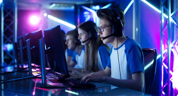 team of teenage gamers play in multiplayer pc video game on a esport tournament. captain gives commands into microphone, trying strategically win the game. - esports stock photos and pictures