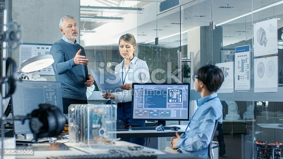 968289374istockphoto Team of Three Engineers and Technicians Discuss New Project. They Work in Technologically Advanced Center of Computer Science. 968289566