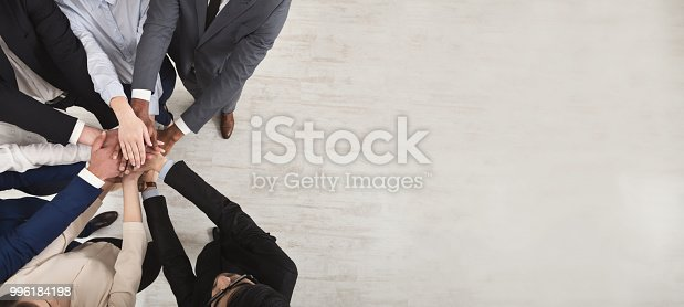 istock Team of united coworkers standing with hands together 996184198