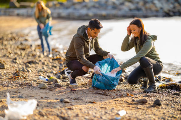 Team of volunteers collecting garbage at beach stock photo