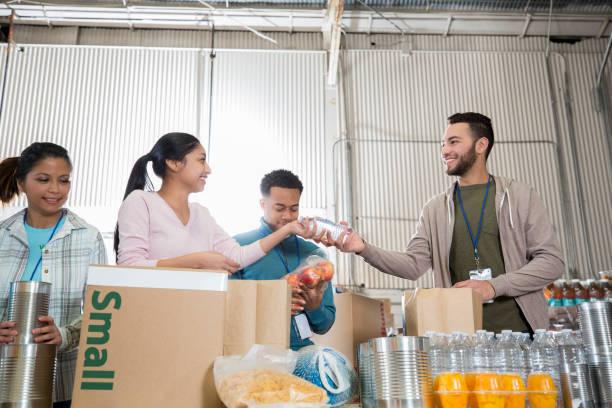 equipe de voluntários classifica mercadorias no banco de alimentos - charity and relief work - fotografias e filmes do acervo