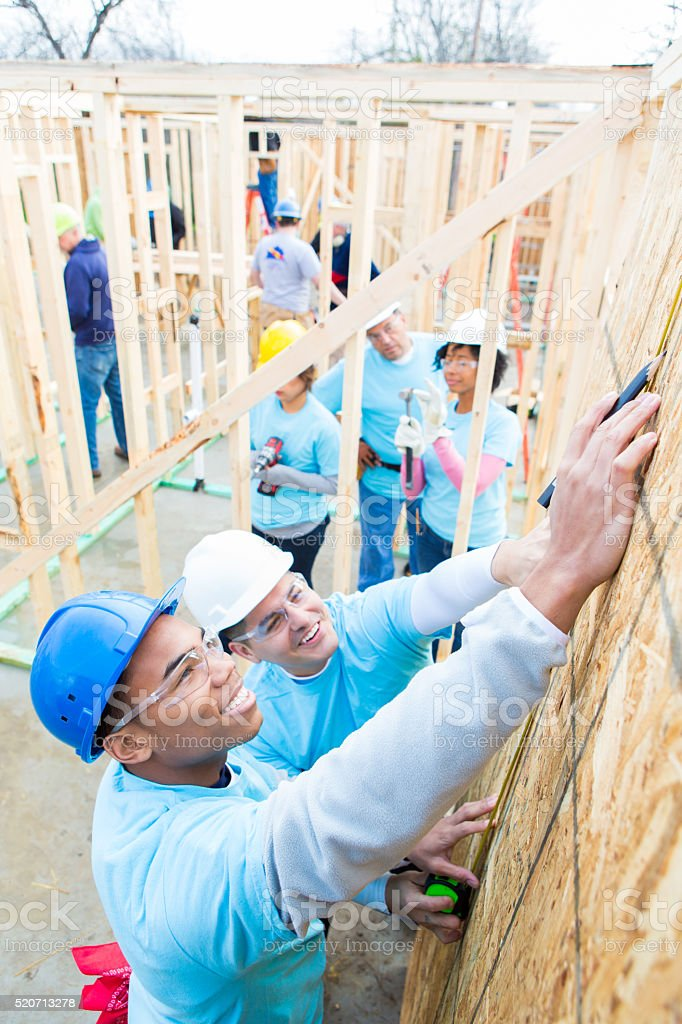 Team of volunteers work together to build home stock photo