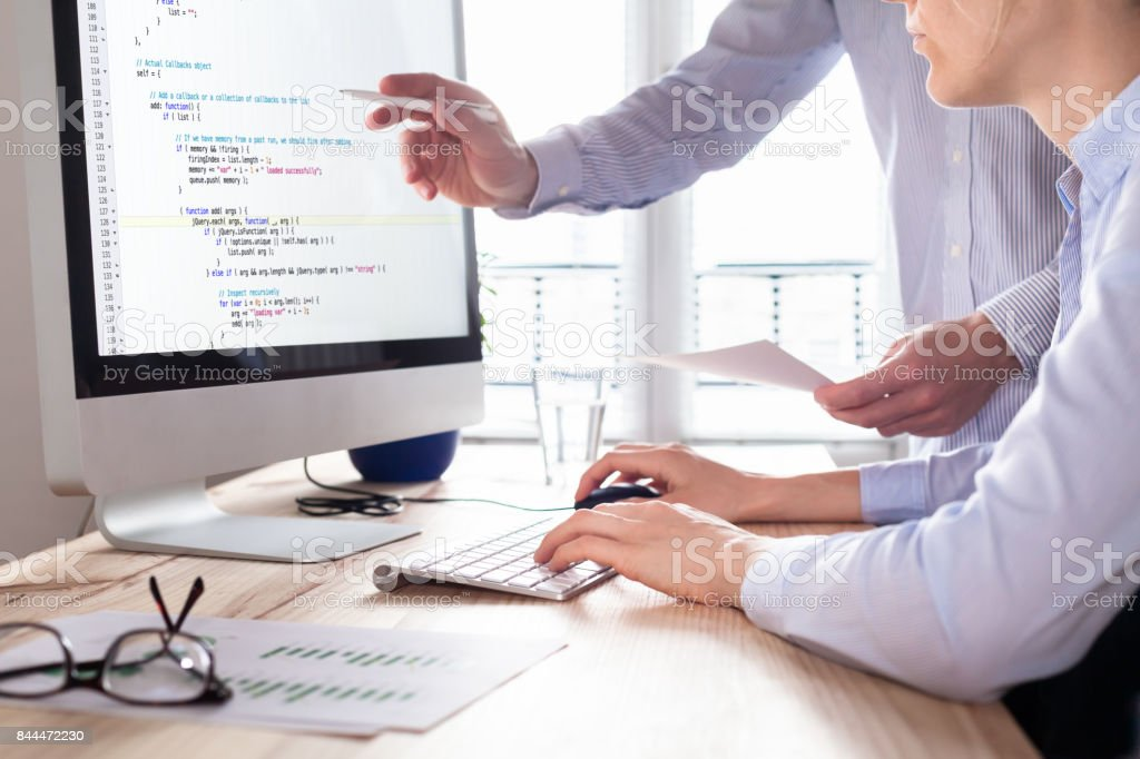 Team of web app developers coding website source code, debugging stock photo