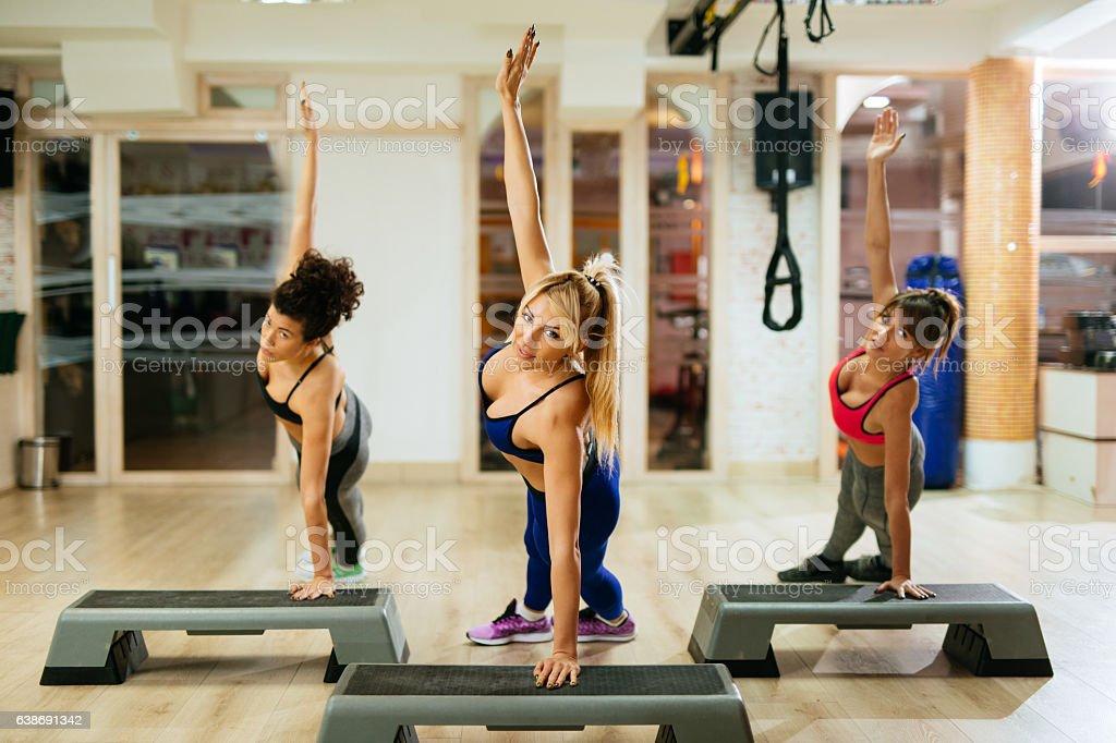 Team of women exercising step aerobics at the gym. - foto de acervo