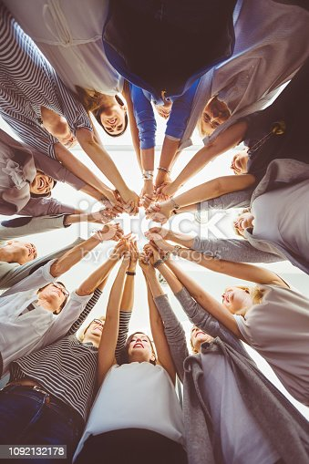 Low angle view of women standing in a circle holding hands. Trust and team work concept.