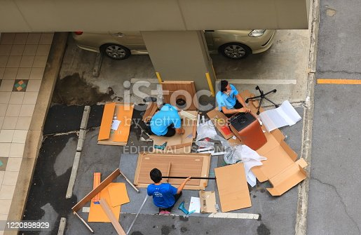 Bangkok Thailand- April 25 2020: A team of three workers are assembling knock down furnitures on parking lot before deliver to customer.
