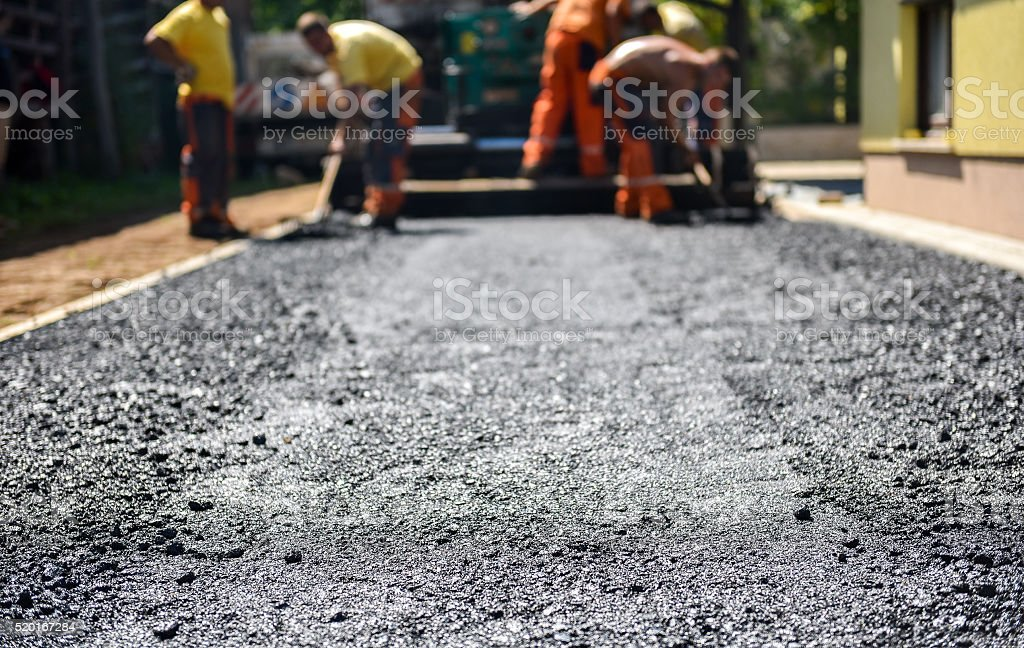 Team of Workers making and constructing asphalt road constructio​​​ foto