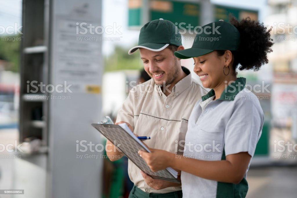 Team of workers working at a gas station stock photo