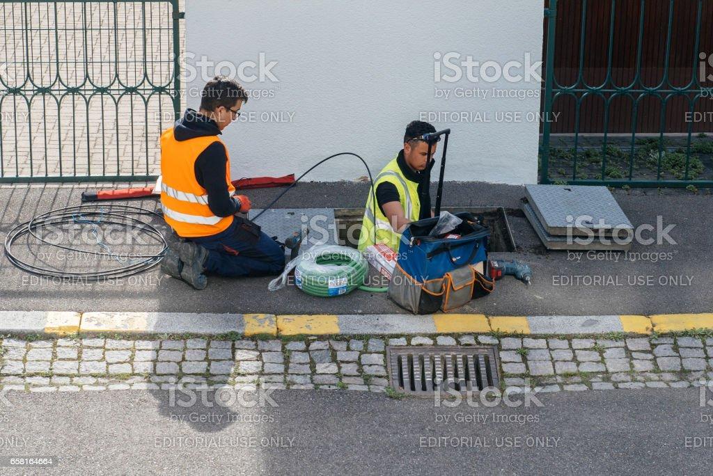 Team of workers working on implementation of fiber optic cables in sewage system foto de stock libre de derechos