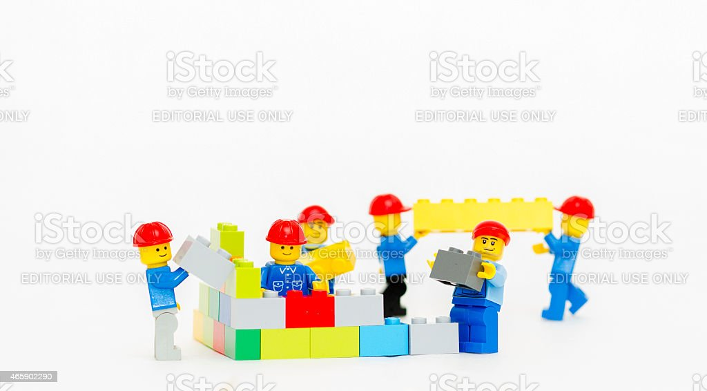 Team of workman Lego mini figure build a wall. stock photo