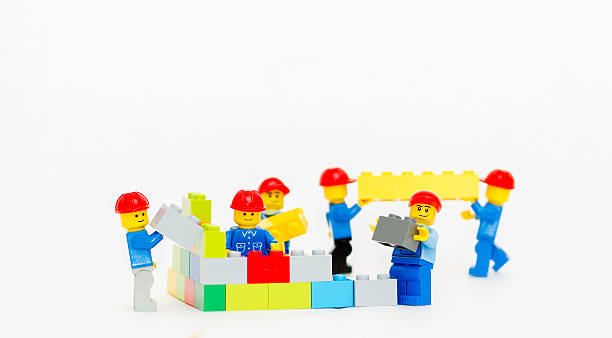 team of workman lego mini figure build a wall. - lego stok fotoğraflar ve resimler
