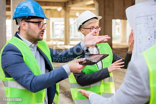 1166176793 istock photo Team of young architects discussing and arguing during a meeting on a construction site 1143211303