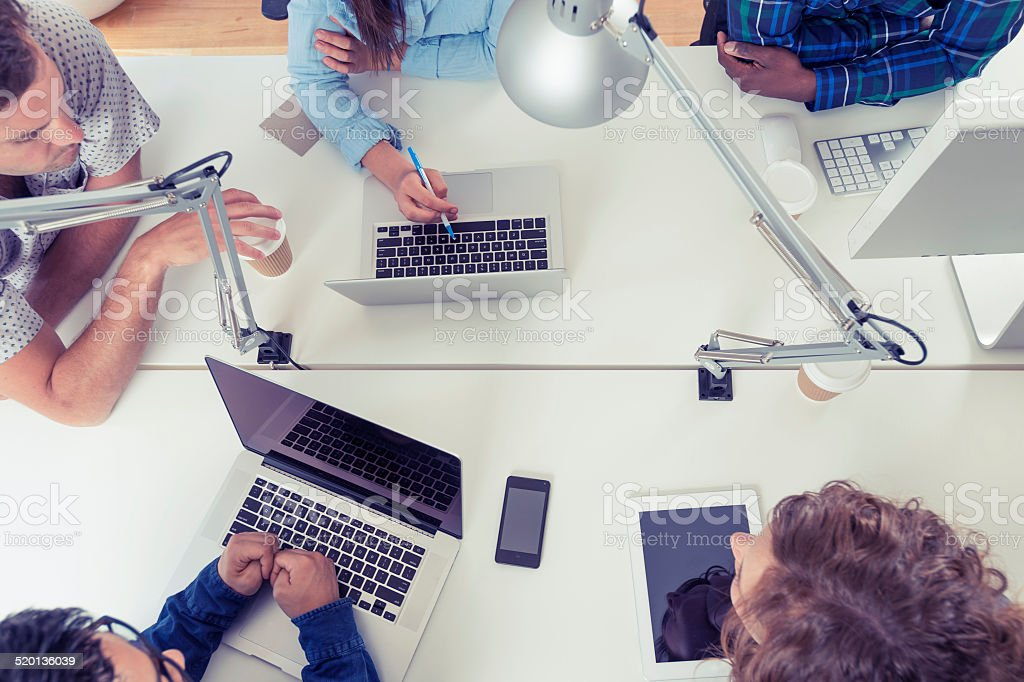 Team of young business people using technology in a meeting stock photo