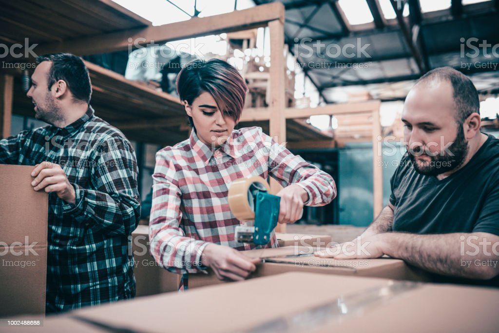 Team Of Young Carpentry Workers Packing Products In Boxes Together stock photo