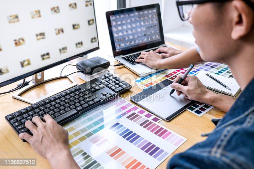 Team of young colleagues creative graphic designer working on color selection and drawing on graphics tablet at workplace, Color swatch samples chart for selection coloring.