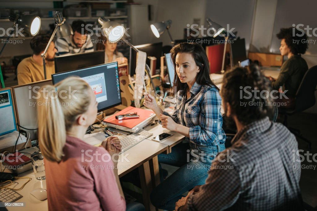 Team of young computer programmers talking in the office. Group of computer programmers working in the office. Focus is on woman in shirt talking to her colleagues. Adult Stock Photo