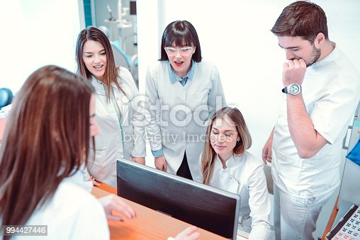 istock Team Of Young Dentists Working On Statistics In Clinic 994427446