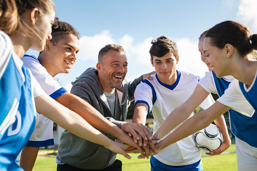 Happy coach and high school soccer team with their hands stacked in football court. Young football players stacking hands together. Mature man coach encourages his students to do their best during the sport match.