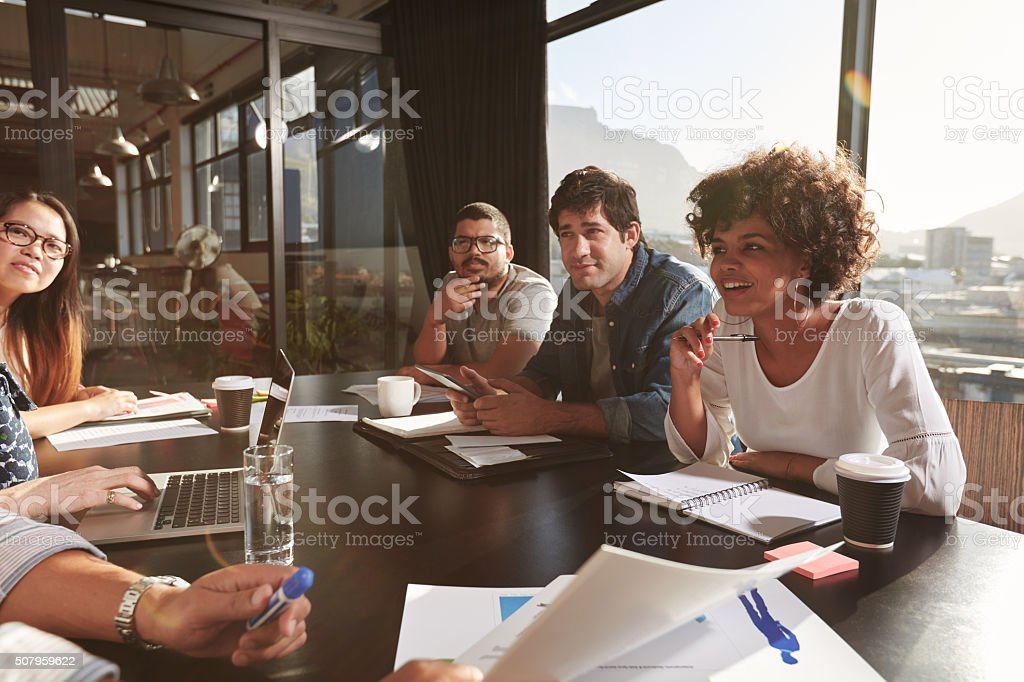 Team of young people discussing new business plan stock photo