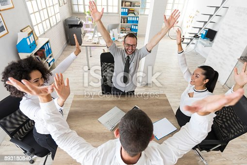 1016771914 istock photo Team of young people holding hands in modern workplace 893180840